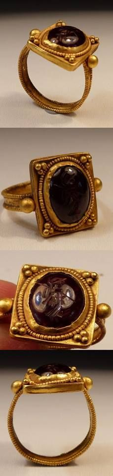 Roman Gold Ring having a flat band decorated with beaded filigree supporting a large square bezel with oval raised filigree mount set with a carved gem stone intaglio, showing Mars. Dating to the 2nd Century CE