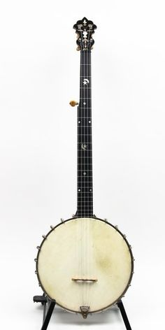 A very fine, classical banjo with 11 inch, spun over, nickel silver rim with rosewood interior has 24 brackets; the cherry neck has a lightly carved heel and fancy stars and moons throughout the fingerboard. Large, mother of pearl flowerpot in peghead. This banjo is extremely clean and original with the exception of a replacement nut..