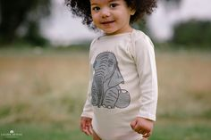 Smiling boy in a grassy meadow wearing an elephant onesie.