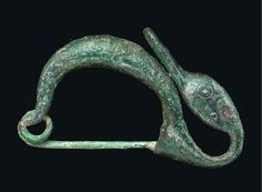 Etruscan bronze fibula with a plain arching bow, a coiled pin at one end, a catch-plate at the other extending into a stylized duck head curved back along the bow, with dotted circle eyes, the elongated bill flat on the underside