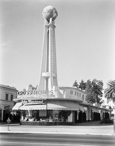Entrance to the Crossroads of the World shopping center designed to look like a Streamline Moderne ship. It has a tall, open tower that is topped with a lighted globe. In the foreground is the John Macsoud shop. It is located at 6671 Sunset Boulevard in Hollywood