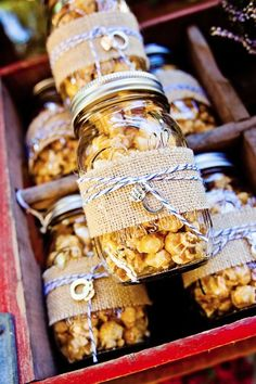 For a fun DIY wedding favor idea... fill mason jars with carmel popcorn or any other treat of your choice, wrap with burlap and guests will love it!
