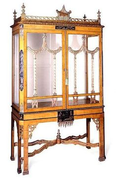 Chinoiserie - A George III style fruitwood and chinoiserie vitrine cabinet. Surmounted by a central gilt pagoda over two glazed doors divided by swag mullions. height 7ft 7in; width 4ft 6in; depth 23 1/4in