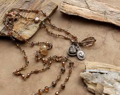 :: High Desert Amulets ::  Heres another offering of my vintage style, a lovely, glimmering necklace of oxidized brass and tiny beads, anchored with three small amulets at the bottom. This is the kind of piece you can wear just about anywhere and it will look good, and it has a very nice drape thanks to the dozens of tiny links. It is also sturdy, and a great piece to layer with others. The warm, earthen hues light up and blend well with so many things...or they look perfect on their own…
