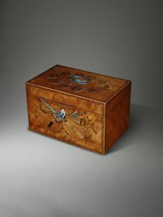 OnlineGalleries.com - A fine late 18th century George III satinwood and marquetry tea caddy inlaid satinwood, marquetry, tulipwood, with a panel depicting a musical trophy.  4.72 inches high  7.87 inches wide  4.92 inches deep