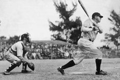 Profile of American baseball player Babe Ruth (George Herman Ruth, 1895 - 1948) swinging at bat as a catcher crouches behind him during a game.