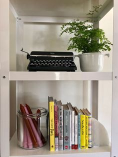A vintage typewriter and a Maidenhair fern with travel books and a jar of candles