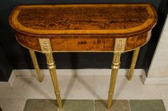 A pair of Sheraton figured mahogany and satinwood banded D-form console tables on turned and fluted gilt legs headed by paterae. Possibly American. PERIOD: 1780-1789| From a unique collection of antique and modern console tables at https://www.1stdibs.com/furniture/tables/console-tables/