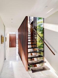 This modern wood staircase matches the wood used on the front door, and is a strong contrast against the white walls and white marble flooring. Arno Matis Architecture together with RUFproject have completed the renovation of a house in Vancouver, Canada. Wood Staircase, Staircase Design, Stair Design, Timber Slats, Wooden Slats, Escalier Design, Modern Stairs, Floating House, Interior Stairs