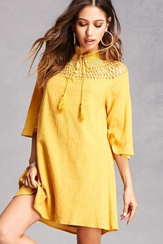 A crepe woven mini dress featuring a semi-sheer floral crochet mock neck with long tasseled self-ties, a front three-button placket, a semi-sheer crisscross crochet design on bodice, long bell sleeves, and a billowy silhouette.<p>- This is an independent brand and not a Forever 21 branded item.</p>