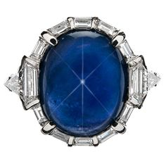 Art Deco 1930's. A clear and distinct star is present in this heavenly 8.81 carat, natural Burma star sapphire. The deep midnight blue of this luscious stone captivates. Framing the sapphire are ten emerald cut baguette diamonds with two trapezoids and trillion cuts accenting the ring's shank. A spectacular museum quality Art Deco Original.