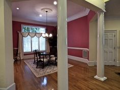Formal dining room with hardwood floor, chair rail, crown molding, columns, recessed lights and ceiling medallion