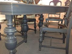 "This gorgeous dining room table features four ornately carved chairs. All of the pieces have been refinished in neutral classic black and lightly distressed. The table has unique legs with very pretty turnings. There is one additional leaf for the table which measures 12"" wide that is stored underneath the table."