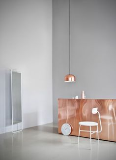 The GM—Grethe Meyer—Pendants are balanced pendant lights that can be used for overhead lighting in a dining room or kitchen, and can also be grouped together to create a graphic lighting installation. Shown here, the GM 30 Pendant Light in Copper is made of lacquered solid copper and is suspended from a black fabric cord. Shown with Menu's Afteroom Chair, Kaschkasch Mirror, and Marble Wall Clock.
