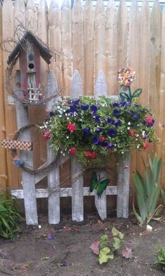 Love the small fence & birdhouse in flowerbed