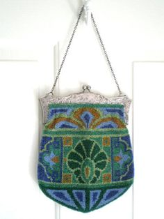 """Antique Art Nouveau Glass Beaded Purse late 19th-Century, tulip-shaped, crafted of small to medium glass beads approximately 16 beads per inch, in a vibrant color palette of cobalt blue, lilac, copper/amber, forest green, emerald green, & sage— lavish, classic Art Nouveau design (same on both sides) w/ a stylized lotus; heavy nickel silver frame w/ intricate, intertwining floral & foliate patterns on both sides, large ball kiss clasp & 16"""" medium link chain; 8""""w x 10"""" h; frame 7-1/2"""" x…"""