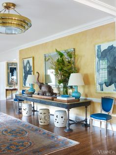 Chairs upholstered in royal blue silk aside turquoise ceramic lamps supply symmetry and color in this entry hall. Vintage French table. Garden stools, Treillage. Swedish 18th-c. chairs, Steven Sclaroff. Lamps, Daniel Barney. Pendant, Charles Edwards. Rug, Doris Leslie Blau. Art, Sarah Graham. Image originally appeared in the January/February 2013 issue of VERANDA.INTERIOR DESIGN BY BUNNY WILLIAMS   - Veranda.com