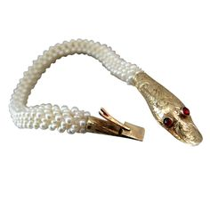 Contemporary woven seed pearl rope bracelet with antique gold and ruby snake clasp.