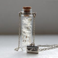"Dandelions seem to follow me through this life. I welcome it, of course, it's one more shot at making a wish come true. This necklace is part of my Take Flight Collection. Feel free to uncork the bottle and make a wish. These make GREAT birthday presents!! Each comes packaged in a clear jewel case with a tiny ""as you wish"" banner (as seen in the last photo) perfect for gift giving! The bottle stands about 2 inches tall (including cork) and about 1/2"" wide. Chain is about 24"" long and can be…"