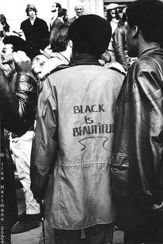 """ On Feb. 1970 veteran photographer Ilke Hartmann attended a Black Panther Party rally in SF. She came across a teenager walking through the crowd with the words, ""Black Is Beautiful"" handwritten on his jacket. Black Panther Party, By Any Means Necessary, Black And White Aesthetic, Power To The People, My Black Is Beautiful, Black Power, Black People, Oeuvre D'art, Belle Photo"