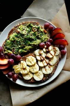 two slices of whole wheat bread: one topped with guacamole, cress, lemonjuice and hempseeds and one topped with almondbutter/peanutbutter, banana slices and hempseeds and some fresh fruit on the side