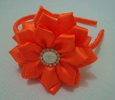 Tiara com linda flor e botão decorativo com strass. R$ 19,90