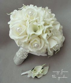 Purple roses, white calla lilys with brooches/pearls in it.