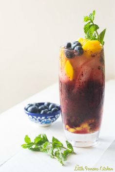 Blueberry Mango Mojito | Guest Post for #BoozeWeek from The Little Ferraro Kitchen on Cravings of a Lunatic | These blueberry mango mojitos are the epitome of summer! The colors are vibrant and the fruit sweet as a summer breeze.
