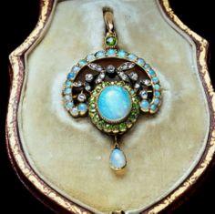 A late Victorian Art Nouveau opal, demantoid garnet and diamond pendant, an oval opal surrounded by demantoid garnets, with openwork diamond...