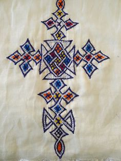 White, long sleeved traditional Ethiopian dress with blue and red cross embroidered motif