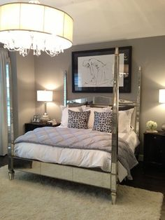 Mirrored four poster bed, gray paint, silver lamps and chandelier.