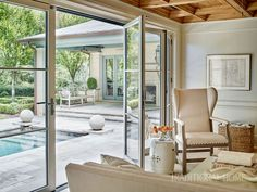 In this cozy pool den, a wall of glass bifold doors makes it easy to blend indoors and out. - Photo: Emily Jenkins Followill / Design: Suzanne Kasler