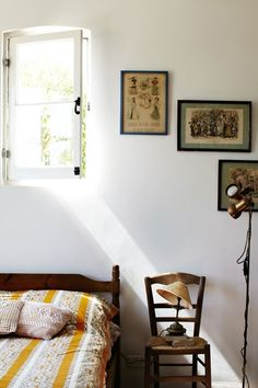 Perfect combination of bare(ish) white walls, warm wood pieces, and colorful textiles. I like the lamp on the chair.