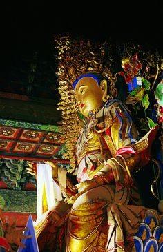 """A statue of Manjusri, also known as the Bodhisattva of supreme wisdom, with a full, round face and elongated ear lobes. She rides a legendary beast of prey and has an ornate five-Buddha crown on her head. From """"Buddhist Buildings,"""" a volume of the Library of Ancient Chinese Architecture."""