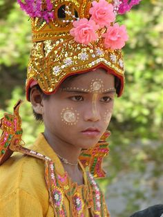 Burma  (A boy putting on a ceremonial dress and makeups at a Buddhist Ceremony before becoming a Temporary Buddhist Novice.  This is a Traditional Buddhist Cultural Practice in Burma/Myanmar)
