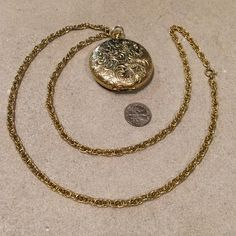 """Time-Piece Style Locket on Long Gold Tone Chain Pocket watch, time-piece style locket and long chain statement necklace. Gold tone, my best guess, gold-plated brass, but not 100% sure. Engraved daffodils, and feathered swirls decorate the light locket. A push-button mechanism opens the locket as would be on a pocket watch. Locket is 2"""" diameter. 26"""" chain has nice weight to it but too heavy. Classic Victorian or Edwardian Style. Perfect gift for the Downton Abbey enthusiast. Vintage Jewelry…"""