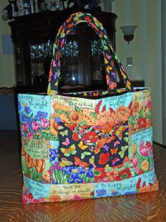 The pattern is Charm Party Tote by Penny Sturges, fussy cut from a panel by Debi Hron for Timeless Treasures. The lining and pockets are also by Debi Hron for Timeless Treasures.