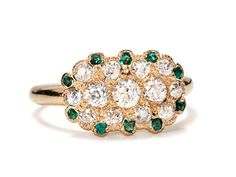 With a bold sweep of color, a surround of ten (10) vividly green hued emeralds dots the perimeter of the matrix with a gently undulating border. Interspersed among the emeralds are eight (8) additional old European cut diamonds which bring the estimated total diamond weight to .50 carats (H-J color range; VS1-SI1 clarity) yet the placement of the diamonds gives the impression of a great deal more diamond size.    Date: Circa 1920.