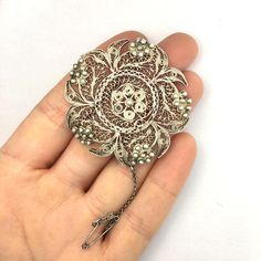 A sizeable solid silver filigree brooch in an intricate flower design with cannetille detail. A handmade piece which would have involved a lot of work to make! Could easily be worn as a pendant. In very good antique/vintage condition. Fixes with a C clasp with a safety chain for