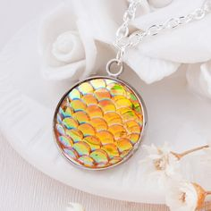 A gorgeous iridescent scales necklace, perfect for mermaid or dragon fans! Girly meets myth and magic these necklaces are eye catching and truly beautiful! Chain Length : 49cm Pendant Size : 23mm*20mm