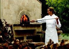 "Andrea adjusting the fire within the Mugnaini Model 180 oven at ""The Art of Wood-Fired Cooking"" school in Healdsburg, CA."