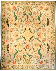 A highly-decorative mid 20th century Portuguese Needlework rug, the cream field with a mirrored design of luxurious green scrolling vinery, palmettes and racemes around a leafy medallion within a floral vinery border. Watch full size video of A Portuguese Needlework rug, Circa 1940, ID BB3929 - Video