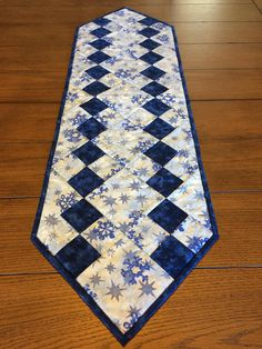This snowflake tablerunner measures approximately 39.5x11.5 inches. The pictures do not do this runner justice. The lighter color fabric is a light blue with snowflakes on it. Gold flecks run threw the snowflake fabric. Would look great on your dining table and can be kept out all
