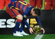 Barcelona's Argentinian forward Lionel Messi displays his fifth Ballon d'Or trophy on the pitch before the Spanish league football match FC Barcelona vs Athletic Club Bilbao at the Camp Nou stadium in Barcelona on January 17, 2016.
