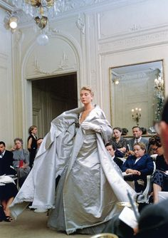 """France presents Dior's evening ensemble called """"Chambord"""", Autumn/Winter Collection H-line, 1954, photo by Mark Shaw, Maison Dior, Paris.  France was one of Dior's star models who managed to be the queen of his catwalk and a constant feature in the French media - she was on the cover of Paris-Match several times. Almost six feet tall, she caught her country's imagination by being blonde and movie-star beautiful."""