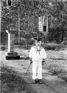 A young boy dressed in a sailor suit stands in front of a sundial in a garden in 1901. Sailor suits were fashionable in the Victorian period as Queen Victoria's own children wore them