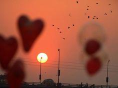 Chegada de 2013 - ÍNDIA - Balões em formato de coração são vistos contra o pôr do sol na Índia enquanto aves voam no céu antes da chegada do Ano-Novo Foto: AP