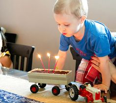 The birthday boy has his very own cake.... in a trailer pulled by his own tractor! So cool!  :-)