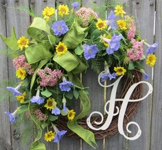 This wreath is the perfect personalized accent for spring and summer! A wired green faux silk ribbon makes a wild bow. Beautiful, realistic baby sunflowers, queen annes lace, petunias, and fern surround the bow. This wreaths fern and blooms have a light and airy feel where the grapevine base is visible in places. A lovely antique white monogram provides a personal accent.  Average Diameter (tip to tip): 21 This wreath was made on a grapevine wreath measuring approximately 18  Indoor/ She...