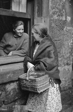 Two women chatting through an open window in the Gorbals area of Glasgow The Gorbals tenements were...
